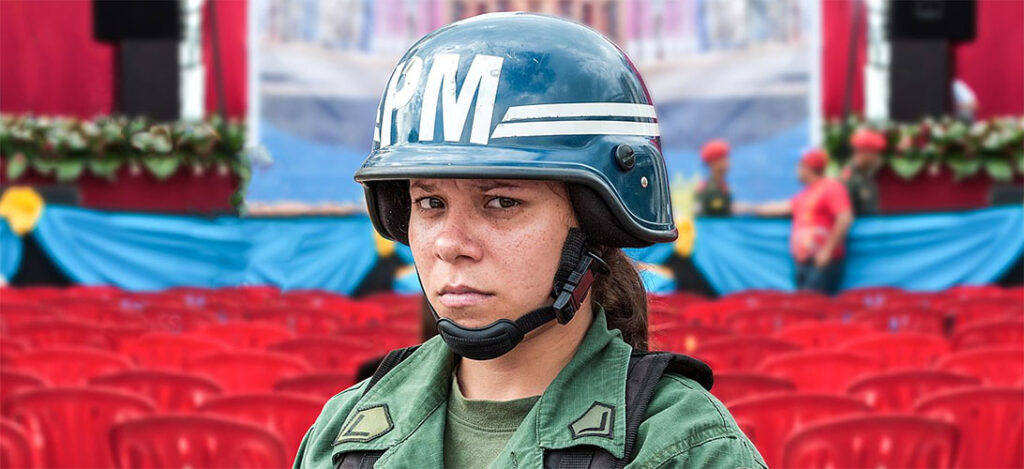 A female soldier looks uneasily into the camera at a political event in Caracas