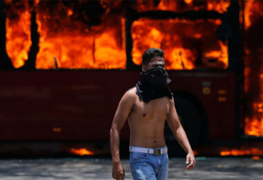 A protester walks in front of a burning bus in Caracas, Venezuela
