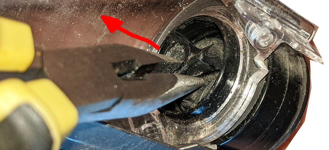 Using a round-nose pliers to pull out the cog driving the spinning brush in a Dyson DC35 motorised head